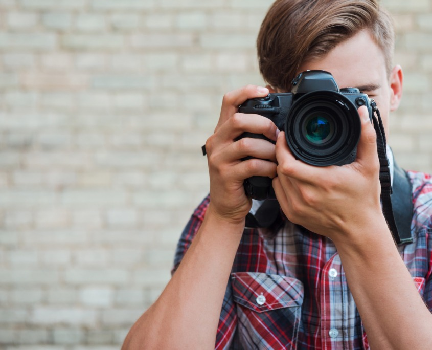 Man with camera in front of brick wall